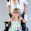 Stock Photo: Smiling little girl sitting on wheelchair