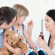 Professional female doctor giving syrup to a little girl — Stock Photo