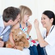 Professional female doctor giving syrup to a nice little girl — Stockfoto