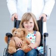 Stock Photo: Portrait of little girl sitting on wheelchair supported by