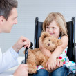 Stock Photo: Smiling little girl sitting on wheelchair lokking at doc