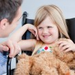 Laughing little girl sitting on the wheelchair — Stock Photo