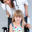 Stock Photo: Smiling cute girl sitting on wheelchair