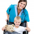 Stock Photo: Nice female doctor carrying adorable little boy in wheelchai