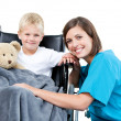 Nice female doctor carrying adorable little boy with his teddy b — Stock Photo