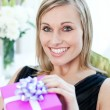 Glowing woman opening a gift sitting on a sofa — Stock Photo