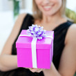 Blond woman opening a gift sitting on a sofa — Stock Photo