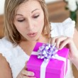 Surprised woman opening a gift sitting on the floor — Stock Photo