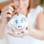 Blond woman saving money in a piggy-bank — Stock Photo