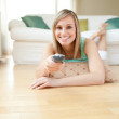 Jolly young woman watching TV lying on the floor — Stock Photo #10305161