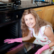 Smiling woman cleaning the oven — Stock Photo #10305821