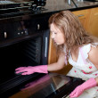 Stock Photo: Tired womcleaning oven