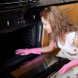 Stock Photo: Young womcleaning oven