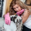 Stock Photo: Tired young womfiling dishwasher