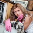 Tired blond woman filing the dishwasher — Stock Photo #10305881