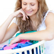 Smiling woman doing laundry - Stock Photo