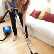 Stock Photo: Portrait of young womvacuuming