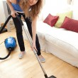Stock Photo: Portrait of bored womvacuuming