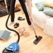 Stock Photo: Young woman vacuuming the living-room
