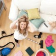 Stock Photo: Frustrated blond womvacuuming living-room