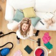 Stock Photo: Stressed blond woman vacuuming the living-room