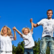 Happy family jumping against a blue background — Stock Photo