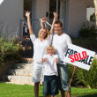 Happy family with their new home in the garden — Stock Photo