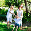 Stock Photo: Happy familiy having fun swinging
