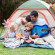 Parents and children playing a guitar in a tent — Stock Photo #10307553