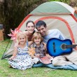 Family camping and playing a guitar — Stock Photo