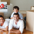 Stock Photo: Happy parents and son lying on the floor after buying house
