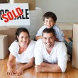 Family on floor smiling at camerafter buying house — Stock Photo #10307947