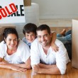 Happy family lying on the floor after buying house with boxes — Stockfoto