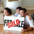 Smiling family on the floor after buying house — Stock Photo #10307961