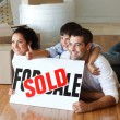 Happy family lying on the floor after buying house with thumbs u — ストック写真