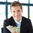 Junior businessman holding dollars and smiling at the camera — Stock Photo