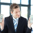 Smiling businessman holding money - Stockfoto
