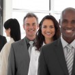 Smiling Business man looking at camera with group in background — Stock Photo