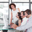 Foto Stock: Female leader managing her team in a call center