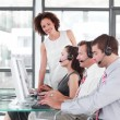 Foto de Stock  : Female leader managing her team in a call center