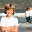 Cute boy on a beach with his parents in background — Stok fotoğraf