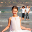 Cute girl on a beach with her parents and her brother in background — Stock Photo