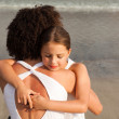 Cute girl and her mother having a hug on the beach — Stock Photo