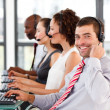 Young businessman working in a call center smiling at the camera — Stock Photo
