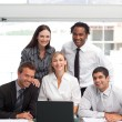 Smiling businessteam working together with a laptop — Stock Photo