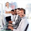 Stock Photo: Smiling female leader managingher team in a call center