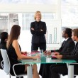 Confident businesswoman smiling at the camera in a meeting — Stock Photo #10309508