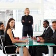Business smiling at the camera in a meeting — Stock Photo #10309510