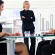 Attractive businesswoman smiling at her colleagues in a meeting — Stock Photo #10309527