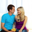 Couple watching television on sofa and eating crisps — Stock Photo #10309553
